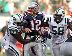 Sept 19, 2011; East Rutherford, NJ, USA; New York Jets defensive end Shaun Ellis (92) and New York Jets linebacker Bryan Thomas (58) put pressure on New England Patriots quarterback Tom Brady (12) during the 1st half at the New Meadowlands Stadium.