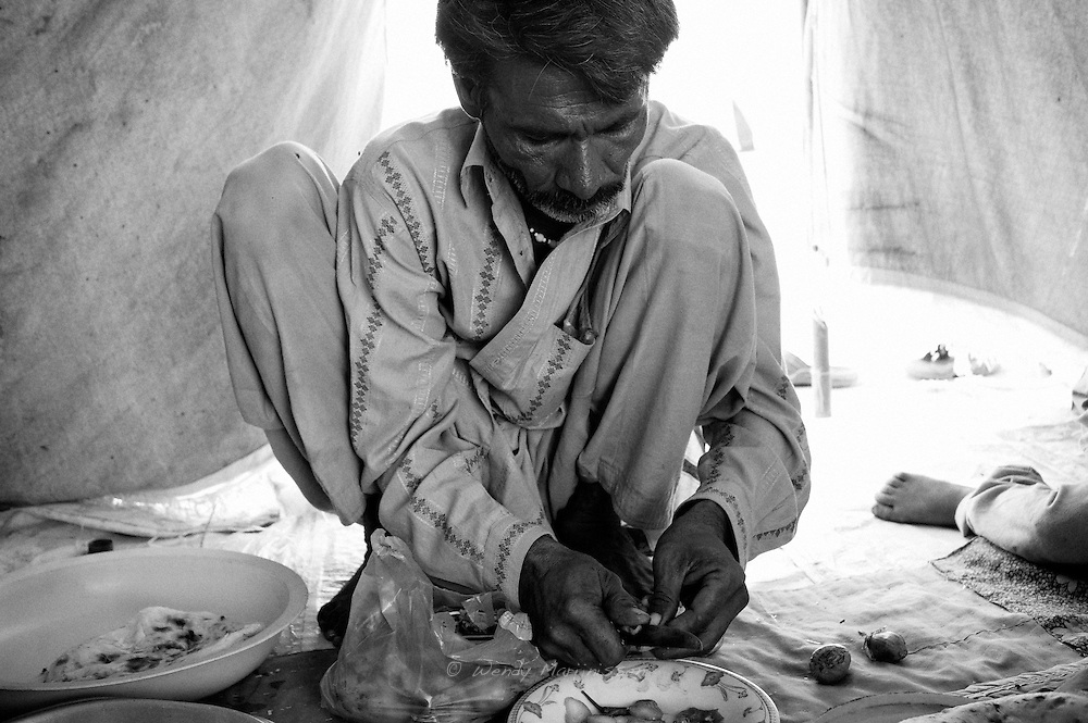 Mohammad Ali is preparing some salad for his children while Hamida is in the hospital for an ultrasound. Karachi, Pakistan, 2010