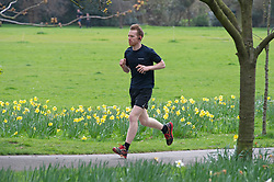 ©Licensed to London News Pictures 20/03/2020<br /> Greenwich, UK. A runner in Greenwich Park. A bright but cloudy day in Greenwich Park, Greenwich, London. Photo credit: Grant Falvey/LNP