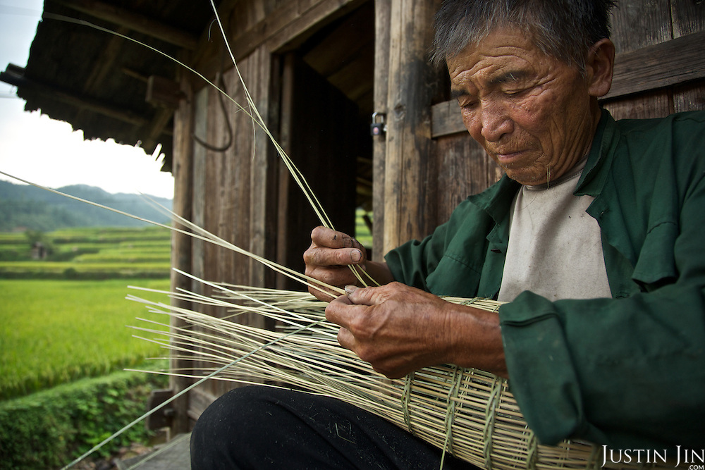 A farmer weaves a fish trap with reed.