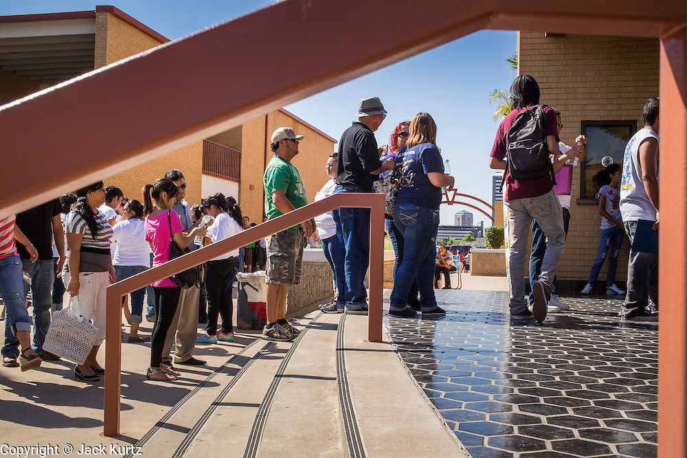 "25 AUGUST 2012 - PHOENIX, AZ:  People wait in line to be let into the deferred action workshop Saturday morning. The line snaked through the parking lot. Hundreds of people lined up at Central High School in Phoenix to complete their paperwork to apply for ""Deferred Action"" status under the Deferred Action for Childhood Arrivals (DACA) program announced by President Obama in June. Volunteers and lawyers specialized in immigration law helped the immigrants complete the required paperwork. Under the program, the children of undocumented immigrants brought to the US before they turned 16 years old would not be subject to deportation if they meet a predetermined set of conditions.    PHOTO BY JACK KURTZ"