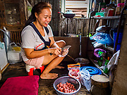 "21 JUNE 2017 - BANGKOK, THAILAND: A woman slices sausages in her home in a community along the Chao Phraya River south of Krung Thon Bridge. This is one of the first parts of the riverbank that is scheduled to be redeveloped. The communities along the river don't know what's going to happen when the redevelopment starts. The Chao Phraya promenade is development project of parks, walkways and recreational areas on the Chao Phraya River between Pin Klao and Phra Nang Klao Bridges. The 14 kilometer long promenade will cost approximately 14 billion Baht (407 million US Dollars). The project involves the forced eviction of more than 200 communities of people who live along the river, a dozen riverfront  temples, several schools, and privately-owned piers on both sides of the Chao Phraya River. Construction is scheduled on the project is scheduled to start in early 2016. There has been very little public input on the planned redevelopment. The Thai government is also cracking down on homes built over the river, such homes are said to be in violation of the ""Navigation in Thai Waters Act."" Owners face fines and the possibility that their homes will be torn down.          PHOTO BY JACK KURTZ"