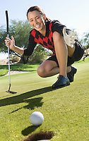 Female golfer looking at ball rolling towards cup
