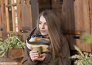 Frau steht vor Holzhuette, mit heissem Getraenk (model-released)