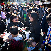 TOKYO, JAPAN - JANUARY 1 : A family laugh together after looking their Omikuji, a Japanese fortune-telling paper strips at Sensoji Buddhist temple in Asakusa district, Tokyo on a New Years day on Sunday, January 1, 2017. Japan celebrated the start of 2017 for the Year of the Rooster. (Photo by Richard Atrero de Guzman/NURPhoto)