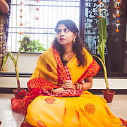 Haldi ceremony before a bengali wedding. Bride waiting for the ceremony to begin. beautiful decoration with banana leaves and flowers in the window. Bride wearing a bright red and yellow cotton saree.