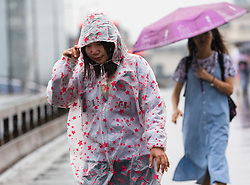 © Licensed to London News Pictures. 27/07/2019. London, UK. Women walk across London Bridge during heavy rain this morning. London and the UK are experiencing heavy rain and stormy weather today following the heatwave and record temperatures during the week. Photo credit: Vickie Flores/LNP