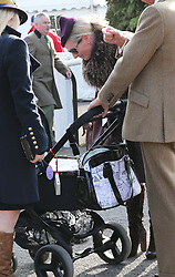 Zara Phillips looks at friends baby in its buggy  at  Ladies Day at the Cheltenham Festival, United Kingdom, Wednesday, 12th March 2014. Picture by Stephen Lock / i-Images