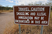 A sign warns visitors of illegal activity in the Gardner Canyon area of the Coronado National Forest in the Santa Rita Mountains in the Sonoran Desert in southern Arizona, USA.
