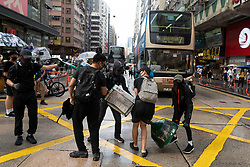 Hong Kong, China. 12th October 2019. Peaceful Pro-democracy march from tourist district of Tsim Sha Tsui along busy Nathan Road to Sham Shui Po Park in Kowloon. Some minor acts of vandalism to property were recorded but most marchers acted peacefully. Evening saw vigil at shrine at Prince Edward MTR  for protestor who died in police custody. Pic. Protestors build small barricade on Nathan Road. Iain Masterton/Alamy Live News.