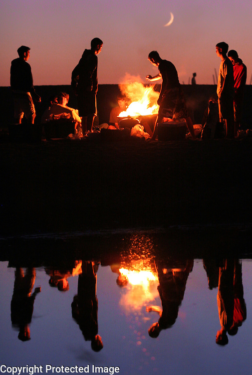 A crescent moon rises over a Twin Lakes State Beach in Santa Cruz, California as a bonfire is reflected in the outflow from Schwans Lagoon on August 14, 2007.