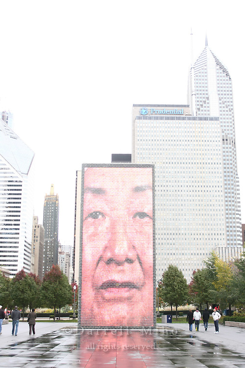 Nov. 08, 2008; Chicago, IL - The Crown Fountain designed by Jaume Plensa...Photo credit: Darrell Miho..The fountain consists of two 50-foot glass block towers at each end of a shallow reflecting pool. The towers project video images from a broad social spectrum of Chicago citizens, a reference to the traditional use of gargoyles in fountains, where faces of mythological beings were sculpted with open mouths to allow water, a symbol of life, to flow out. Plensa adapted this practice by having faces of Chicago citizens projected on LED screens and having water flow through a water outlet in the screen to give the illusion of water spouting from their mouths. The collection of faces, Plensa's tribute to Chicagoans, was taken from a cross-section of 1,000 residents..