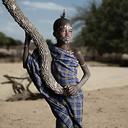 Portrait of Uri Aibila.<br /> <br /> Hamer men wear patterned blankets to protect themselves from the dusty gusts that can blow fiercely during windy season. Hamer woman do not wear same patterns as men.<br /> <br /> Uri was resting on this tree branch on the dry river bank and watching me photograph other people. So I asked him not to move and took his portrait.<br /> <br /> I liked the way that he was leaning comfortably on the branch and how his body, wrapped in his blanket, extended the snaking lines of the brach to the ground.