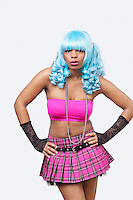 Portrait of cool young African American woman in blue wig over white background