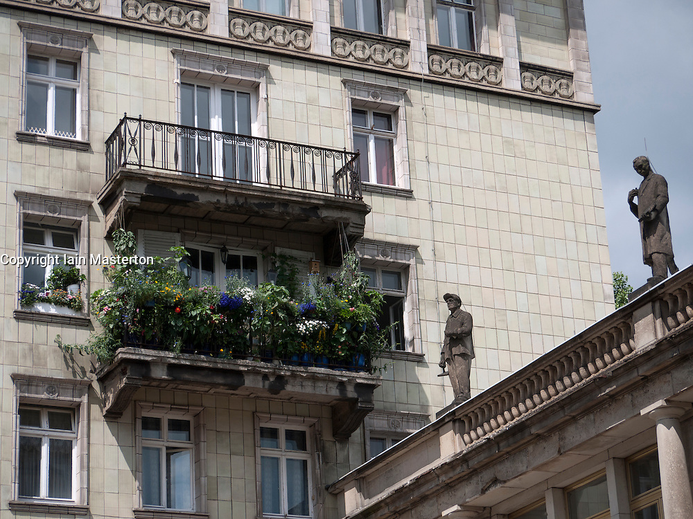 Balcony with flowers and with statue decoration on historic old apartment building on Karl Marx Allee in former East Berlin in Germany
