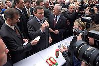 12 MAY 2004, LUDWIGSFELDE/GERMANY:<br /> Gerhard Schroeder (M), SPD, Bundeskanzler, isst eine Grillwurst, umgeben von Journalisten, Personenschuetzern und einigen Schuelern, waehrend dem Besuch der Gesamtschule Ludwigsfelde, Links: Matthias Platzeck, Ministerpraesident Brandenburg, und Rechts: Manfred Stolpe, SPD, Bundesverkehrsminister, <br /> Gerhard Schroeder, Federal Chancellor, is eating a sausage, during a visit of a school near Berlin<br /> IMAGE: 20040512-02-030<br /> KEYWORDS: Gerhard Schröder, Schule, Schüler, Fotografen, photographer, pupil, pupils