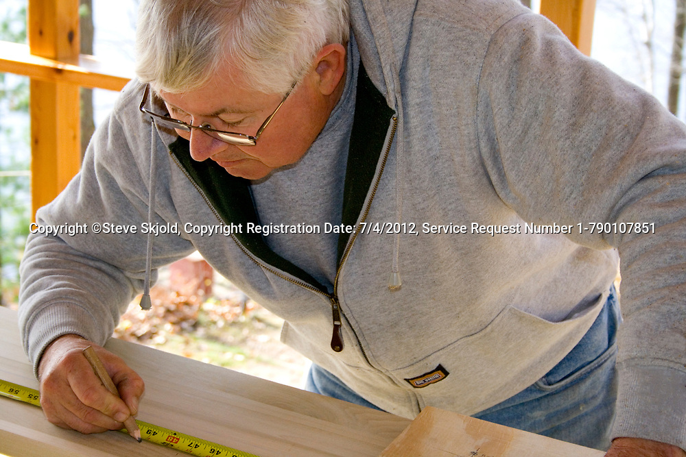 Carpenter carefully measuring board with tape measure for building a porch.  Cumberland Wisconsin WI USA