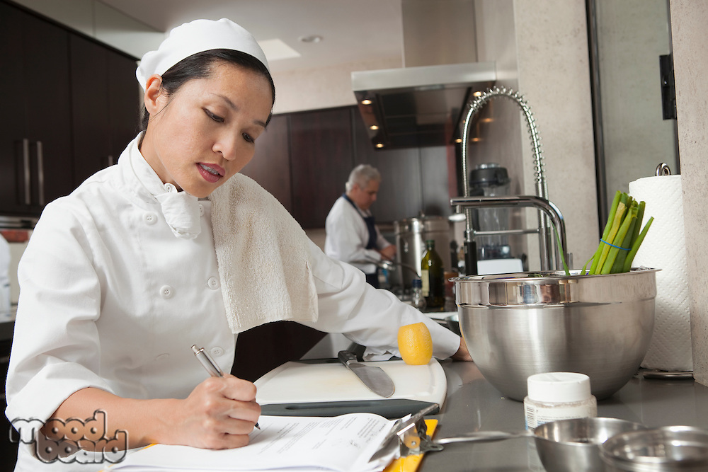Mature chef writing on clipboard