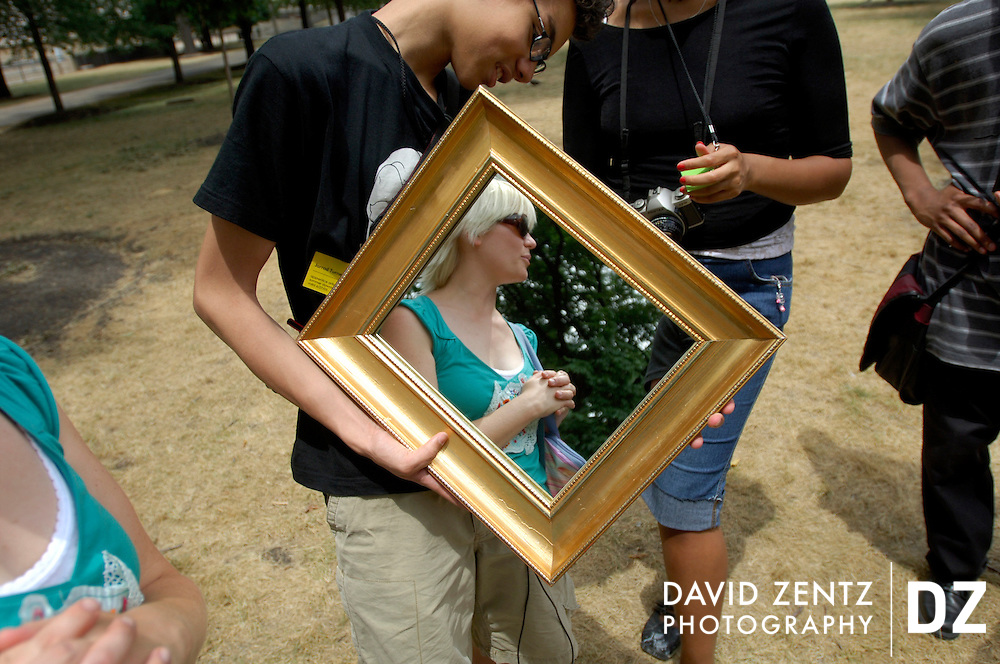 Jarrod Turner holds a mirror reflecting his photo teacher, Karra McDonald, at Grant Park during a Gallery 37 photography course. The students were experimenting with their cameras by taking pictures of the mirror.
