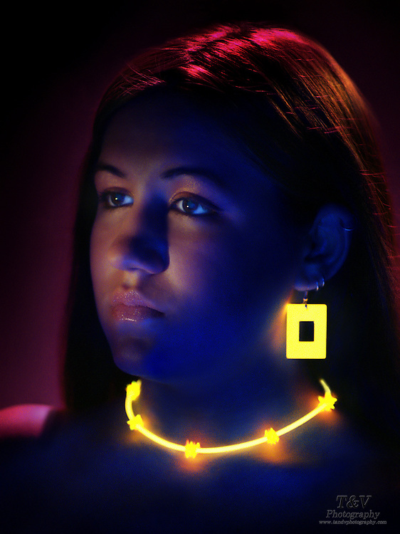 Portrait of a young girl with glowing ear rings and necklace.Black light