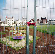 A secure fence deters young children from entering and playing in the new (but as yet unused) playground in the experimental community village of Poundbury, Dorset, England. The new swings and mini-roundabout can be seen through the wire in the foreground while the safe surfaces of wood-chip ensures the little ones are protected from falls on to hard surfaces. Poundbury is the visionary model village that Charles, Prince of Wales sought to develop in 1993 as a successful and pioneering town near Dorchester, built on land owned by his own Duchy of Cornwall, challenging otherwise poor post-war trends in town planning and to some extent following the New Urbanism concept from the US except that the design influences are European.