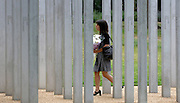 UK - LONDON A woman walks though the memorial carrying flowers as an unofficial ceremony is held in Hyde Park to mark the fifth anniversary of the 7 July bombings in the capital. Survivors and families of those who lost their lives in the terror attacks laid down flowers by 52 steel pillars which represent those killed.<br /> A wreath was laid in the name of Prime Minister David Cameron as a one-minute silence was held at midday. 07 July 2010. STEPHEN SIMPSON