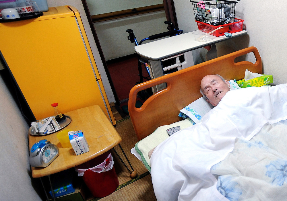 An unidentified elderly man sleeps in his room at a former hotel specially refurbished for the elderly homeless community in the Kamagasaki district of Osaka, Japan. As Japan's population rapidly grays, so too does its homeless community, of which those aged 65 and over are eligible for special governmental benefits that allows them to stay in relatively more comfortable accommodation than their under-65 counterparts. In the central Osaka district of Kamagasaki such accommodation costs around 42,000 yen a month and provides lodgers with communal bath and TV facilities and a 7 sq.-meter room -- barely big enough to fit a single bed and refrigerator.