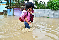 June 15, 2018 - Agartala, Tripura, India - A man carrying a young girl on his back with a bag on his head walks through the flooded water..Indian villagers  are leaving their houses with their children as the flood water has enter their houses after a heavy downpour in Baldakhal village, on the outskirts of Agartala the capital of northeastern state of Tripura, India. National Disaster Response Force (NDRF) personnel are rescuing people, children from different places and bringing them in safe places. (Credit Image: © Abhisek Saha/SOPA Images via ZUMA Wire)
