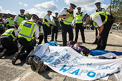 London, UK. 4 September, 2019. Metropolitan Police officers approach anti-nuclear activists who had succeeded in locking themselves together using an arm tube to block one of the two main access roads to ExCel London during protests on the third day of a week-long carnival of resistance against DSEI, the world's largest arms fair. The third day's protests were organised by the Campaign for Nuclear Disarmament (CND) and Trident Ploughshares.