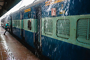 A man leaps into a train as the monsoon rain splashes onto the railway platform.