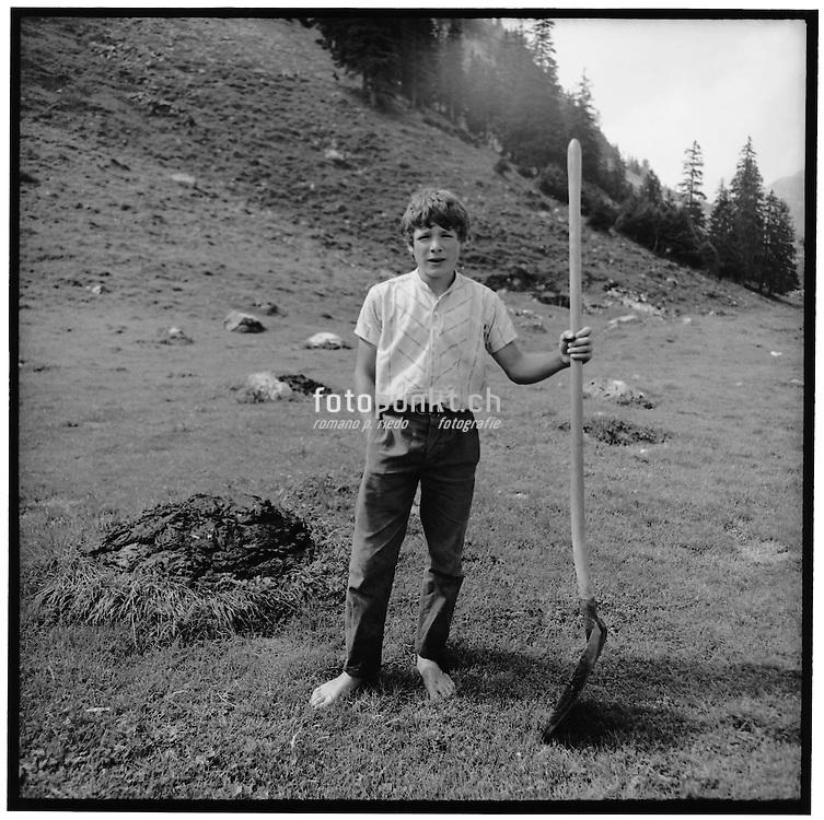 Young boy barefoot on the grass holding a dustpan, garçon de châlet, nu pied avec une pêle à ramsser le fumier; Furglenalp, der Alpbursche barfuss mit der Mistschaufel