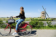 Bij Oegstgeest rijdt een meisje op een stadsfiets langs een windmolen.<br /> <br /> Near Oegstgeest a girl cycles on a city bike near a wind mill