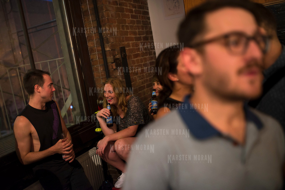 "August 27, 2014 - New York, NY :  Sofar Sounds, which produces ""secret"" concerts in volunteers' apartments in 37 countries, threw a listening party for the debut of Karen O's new solo album ""Crush Songs"" -- with performances by the band ""BOYTOY"" and Julia Easterlin -- in Tribeca on Wednesday evening. The evening concluded with a surprise appearance, and performance, by Karen O and Moses Sumney. Pictured here, audience members drink beer and chat as they find spots to sit in anticipation of the concert. CREDIT: Karsten Moran for The New York Times"