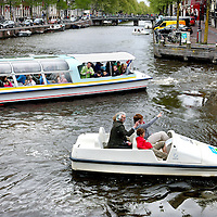 Nederland, Amsterdam , 10 mei 2013..Watertaxi's , waterfietsen en rondvaartboten zitten elkaar regelmatig in de weg in de grachten van Amsterdam zoals hier op de Keizersgracht..Water taxis, sightseeing boats and pedalos obstruct each other regularly in the canals of Amsterdam.