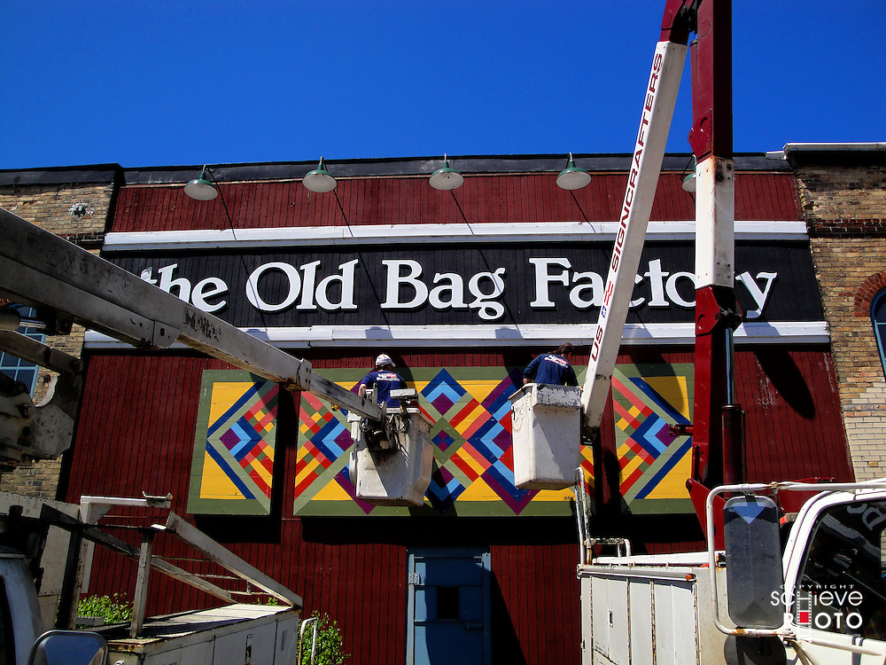 Two workers clean the sign at the Old Bag Factory shops in Goshen, Indiana.