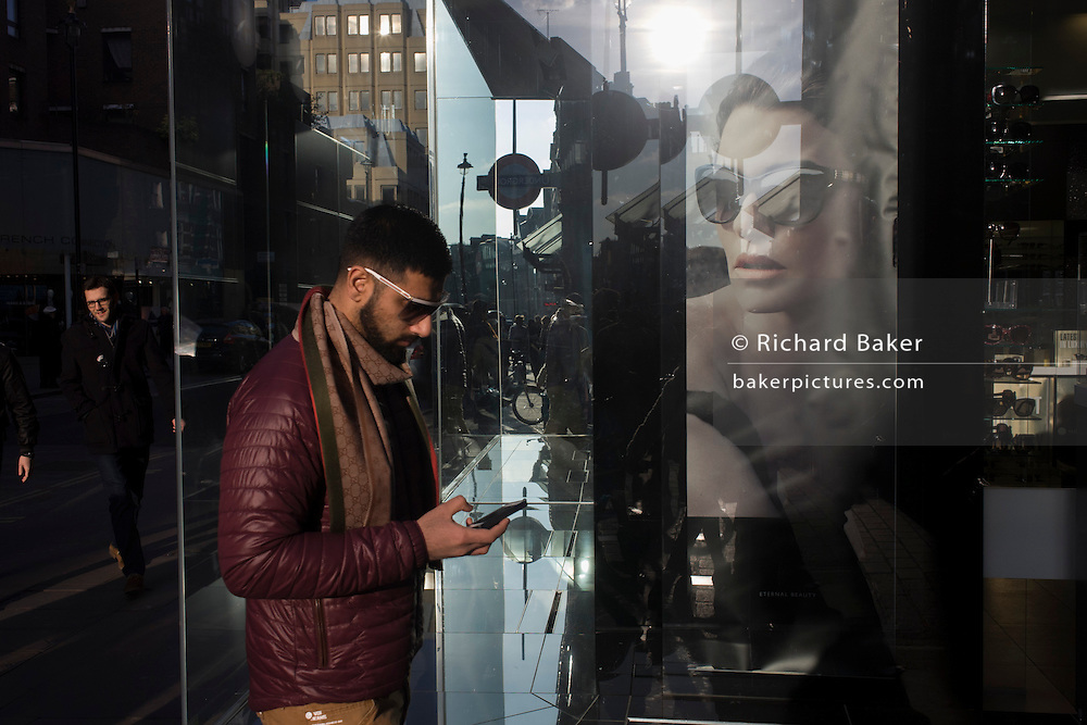 A man walks past a healthy poster girl for Burberry sunglasses they call Eyewear, in a sunlit London street. With the model wearing the glasses looking towards the young male, other Londoners pass-by in this sunlit street. Burberry Group plc is a British luxury fashion house, manufacturing clothing, fragrance, and fashion accessories.