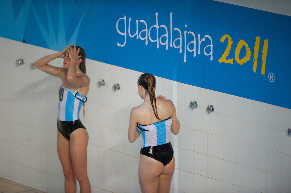 Oct. 21, 2011 - Guadalajara, Mexico - Two girls on the Argentina synchronized swimming team rinse off in the shower after the finals at the Scotiabank Aquatics Center on day seven of the XVI Pan American Games. Canada won the gold medal, USA won the silver, and Brazil won the bronze medal. .©Benjamin B Morris
