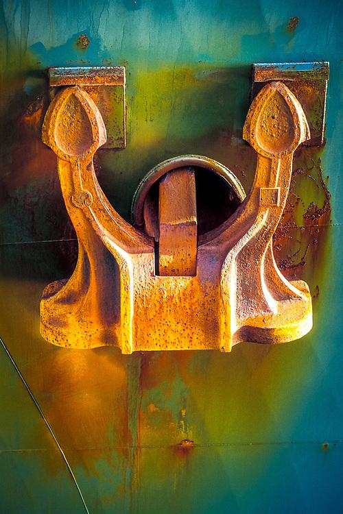 Detail of ship anchor, rust, blue hull, ocean transportation, shipping.