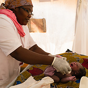 Midwife, Viola Nizigiyimana, examining a healthy baby boy moments after he was born at a Médecins Sans Frontières (MSF) health centre at the Mbera camp for Malian refugees in Mauritania, on 5 March 2013. (In keeping with tradition, the baby will not be named until he is a week old.)
