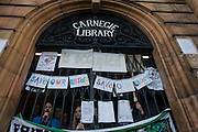 The occupiers of Carnegie Library appear at the building's locked gates in Herne Hill, south London while occupiers remain inside the premises on day 5 of its occupation. The angry local community in the south London borough have occupied their important resource for learning and social hub for the weekend. After a long campaign by locals, Lambeth have gone ahead and closed the library's doors for the last time because they say, cuts to their budget mean millions must be saved.