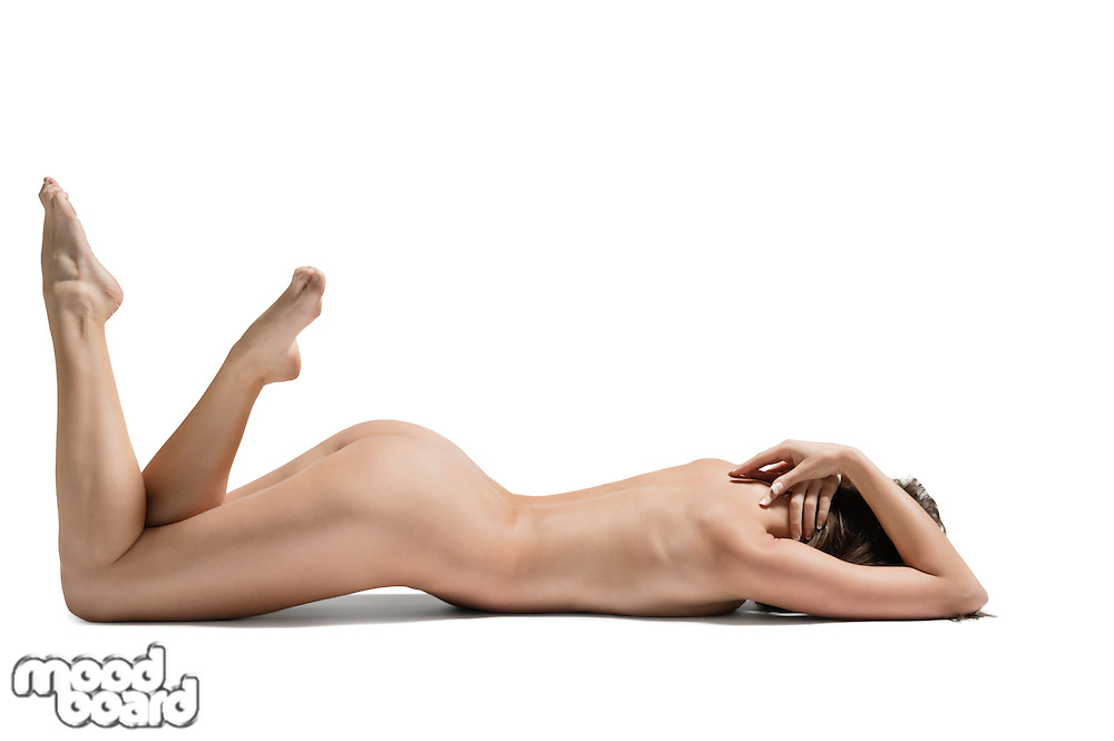 Sexy young naked woman relaxing with legs raised over white background