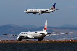 Boeing 737-924(ER) (N69888) operated by United Airlines landing past Boeing 777-346(ER) (JA742J) operated by Japan Airlines, San Francisco International Airport (KSFO), San Francisco, California, United States of America