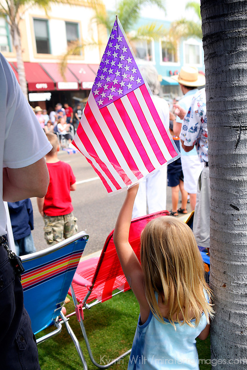 USA, United States, America. Young girl hold American flag (made in China) at the 4th of July parade in Coronado, California.