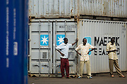 Men stand containers at the sea port in Lome, Togo on Friday October 3, 2008.