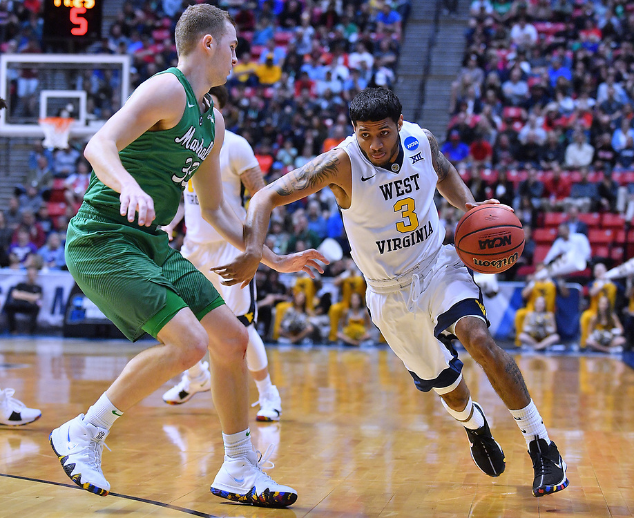 SAN DIEGO, CA - MARCH 18:  West Virginia Mountaineers guard James Bolden (3) drives against Marshall Thundering Herd guard Jon Elmore (33) during a second round game of the Men's NCAA Basketball Tournament at Viejas Arena in San Diego, California.  (Photo by Sam Wasson)