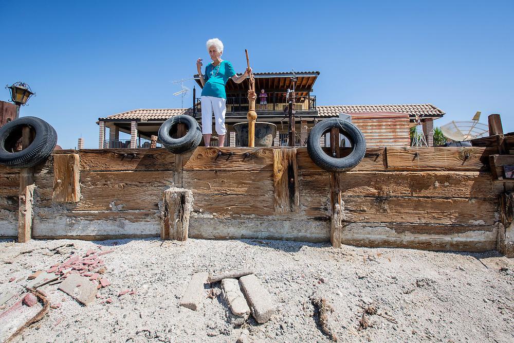 Dottie Friedley (87) ved bryggekanten foran huset i Desert Shores i California. På balkongen bak står ektemannen Chuck (83). Ved stranden rundt Salton Sea i det som en gang var feriemål for kjendiser og rikfolk har vannet sunket med flere meter. Den velbygde brygga har ikke sett vann på flere år, og ingen båt kan legge til. Varmere vær har smeltet snølagrene i fjellene og ført til årelang tørke i delstaten.