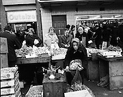 Moore Street, Dublin.      (J97)..1975..23.12.1975..12.23.1975..23rd December 1975..For well over a hundred years Moore Street has served the citizens of Dublin. The longest running open air fruit and vegatable market offers value for money,particularly to those where money is in short supply. Predominately a fruit and veg market there are several traders who sell fish and seasonal goods, as illustrated by the photographs showing turkeys and holly wreaths being sold on the run up to Christmas..image shows a trader bagging veg for a customer. Fruit from all around the world could be purchased here.
