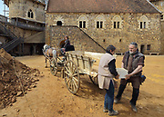 Workers in the courtyard unloading cut stones from a cart pulled by a horse, and behind, the Chapel Tower and the North Range or Logis Seigneurial, at the Chateau de Guedelon, a castle built since 1997 using only medieval materials and processes, photographed in 2017, in Treigny, Yonne, Burgundy, France. The Guedelon project was begun in 1997 by Michel Guyot, owner of the nearby Chateau de Saint-Fargeau, with architect Jacques Moulin. It is an educational and scientific project with the aim of understanding medieval building techniques and the chateau should be completed in the 2020s. Picture by Manuel Cohen