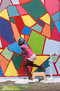A young girl helps paint a new street mural.