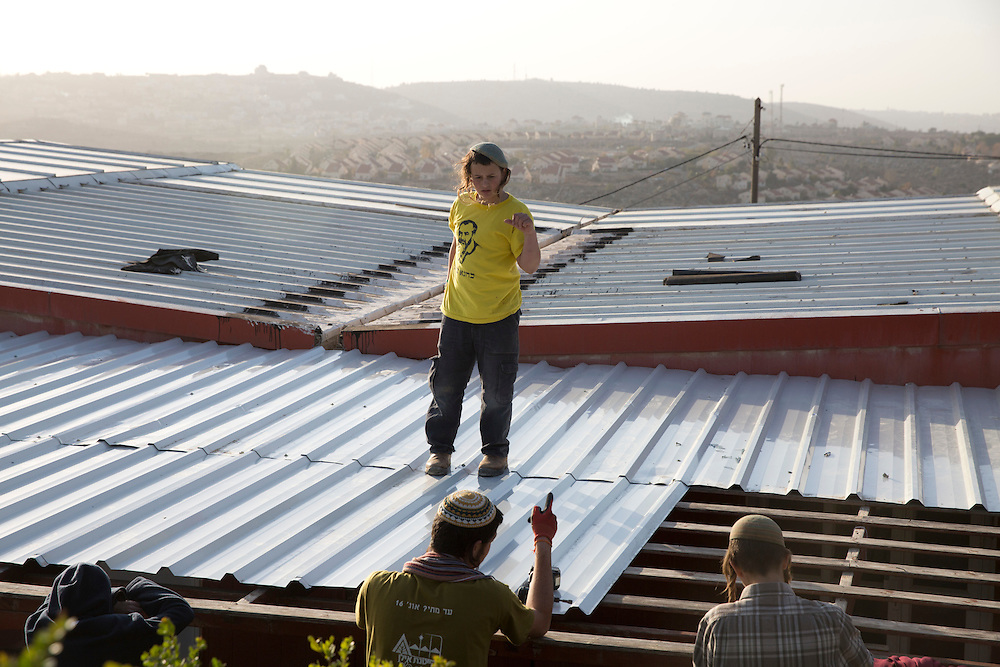 Israeli Jewish settler Azria Shwartz, 13, waring a T shirt showing the late Israeli American Ultra Nationalist and leader of the outlawed Kach party , as he works with others to  build a roof for a synagogue in the West Bank Jewish outpost of Amona on December 7,2016. <br /> Azria was born in Amona and said that despite the Israeli governments decision to move the 40 families from the  illegal outpost t he is determined to stay . He referred to the late Rabbi Meir Kahane as their righteous leader and said that he believed that the Land of Israel was for only the Jews and believes that the Arabs should be moved out to the Arab countries because it is not their land .(Photo by Heidi Levine/Sipa Press).